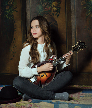 Sierra Hull seated on a carpet playing a mandolin