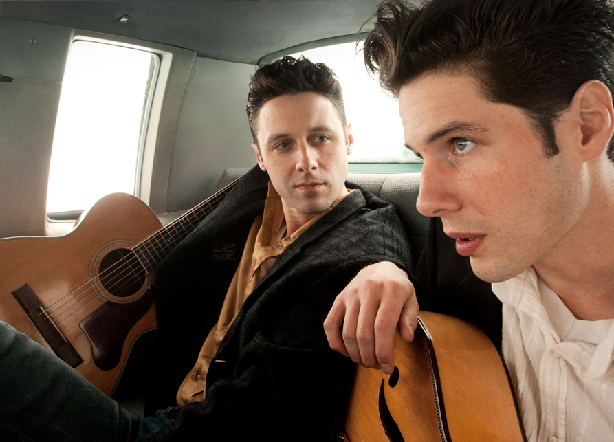 Two men with fair skin and brown hair holding acoustic guitars