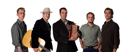 A group of five men; one holds a guitar and another an accordion
